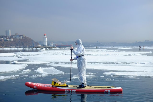 """A sup surfer wearing a protective suit as a show of support for the people fighting against the spread of coronavirus disease takes part at an annual """"Hijacking an ice floe"""" event marking the opening of the stand up paddle boarding season in Vladivostok, Russia on March 21, 2020. (Photo by Ivan Belozyorov/Reuters)"""