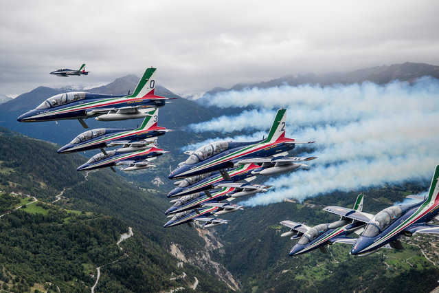 The Breitling DC-3, HB-IRJ, plane fly escorted by Italian Air Force's aerobatic demonstration team, the Frecce Tricolori, during the last stage of its world tour two days ahead of the International Sion Air Show, in Sion, Switzerland, 13 September 2017. From March to September 2017, the Breitling DC-3 from 1940 has done a grand world tour in several stages, over 28 countries and flies 50000km, an amazing accomplishment for this legendary plane that will be celebrating its 77th birthday. (Photo by Christian Merz/EPA/EFE)