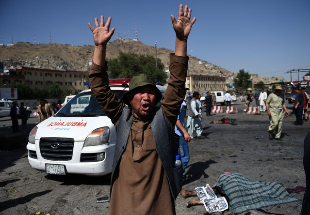 An Afghan protester screams near the scene of a suicide attack that targeted crowds of minority Shiite Hazaras during a demonstration at the Deh Mazang Circle in Kabul on July 23, 2016. Islamic State jihadists claimed responsibility for twin explosions July 23 that ripped through crowds of Shiite Hazaras in Kabul, killing at least 61 people and wounding 207 others in apparently their deadliest attack in the Afghan capital. The bombings during a huge protest over a power transmission line could deepen sectarian divisions in a country well known for communal harmony despite decades of war. (Photo by Wakil Kohsar/AFP Photo)