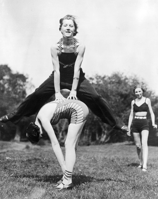 A group of women camping near the River Thames enjoy a game of leap-frog, 1935.