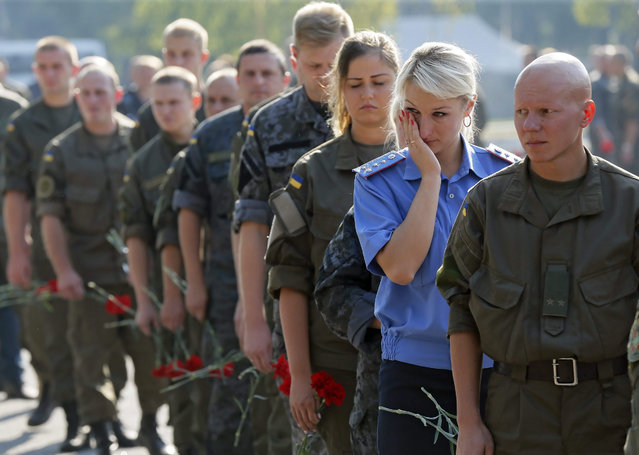 Ukrainian National Guard soldiers attend a funeral ceremony for Igor Debrin (24), who was killed at August 31 during clashes between protesters and police, at Novi Petrivtsi shooting range in Kiev, Ukraine, 02 September 2015. A Ukrainian policeman was killed and more 120 were injured in clashes with protesters outside the parliament in Kiev on 31 August after a vote to give more autonomy to the country's war-torn eastern regions. (Photo by Sergey Dolzhenko/EPA)