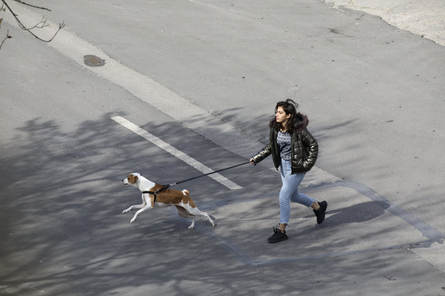A woman walks her dog in a deserted street amid the coronavirus outbreak, in Ankara, Turkey, Sunday, March 22, 2020. (Photo by Burhan Ozbilici/AP Photo)