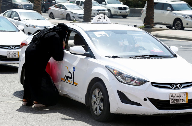 A woman speaks with a taxi driver to get a ride in Riyadh, September 28, 2017. (Photo by Faisal Al Nasser/Reuters)