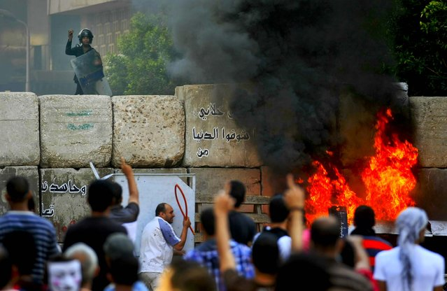 Protesters clash with security forces near the U.S. Embassy in Cairo, Egypt. (Photo by Khalil Hamra/Associated Press)