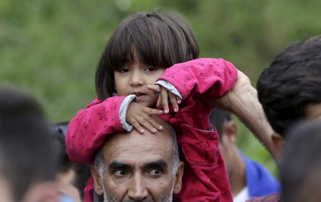 A migrant holds a child as he walks down a street from Keleti train station in Budapest, Hungary, September 5, 2015. (Photo by David W. Cerny/Reuters)