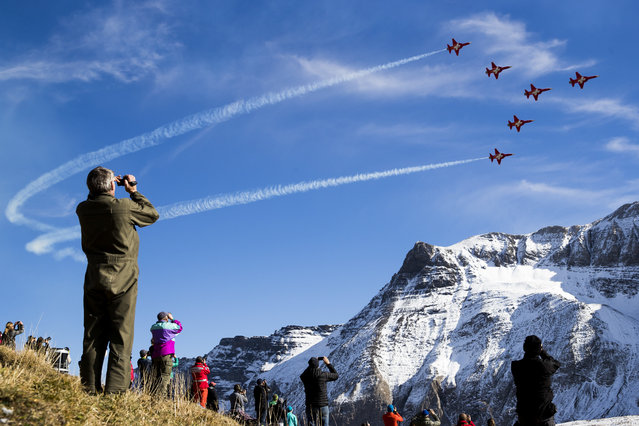 """In this October 10, 2017 photo spectators look to the aerobatic team of the Swiss Air Force """"Patrouille Suisse"""" when the Swiss Air Force pilots show their skills in the Swiss Alps above Axalp Ebenfluh. At an altitude of 2,200 m above sea level, spectators could marvel at a unique aviation display performed at the highest air force firing range in Europe. (Photo by Christian Merz/Keystone via AP Photo)"""