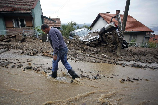 A man walks past damaged vehicles on a street covered with water due to heavy floods in Tekija village September 17, 2014. (Photo by Djordje Kojadinovic/Reuters)