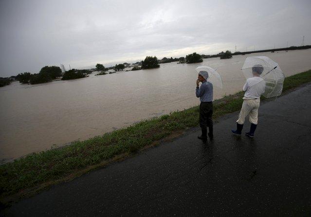Men look at the flooded Kinugawa river, caused by typhoon Etau, in Joso, Ibaraki prefecture, Japan, September 10, 2015. (Photo by Issei Kato/Reuters)