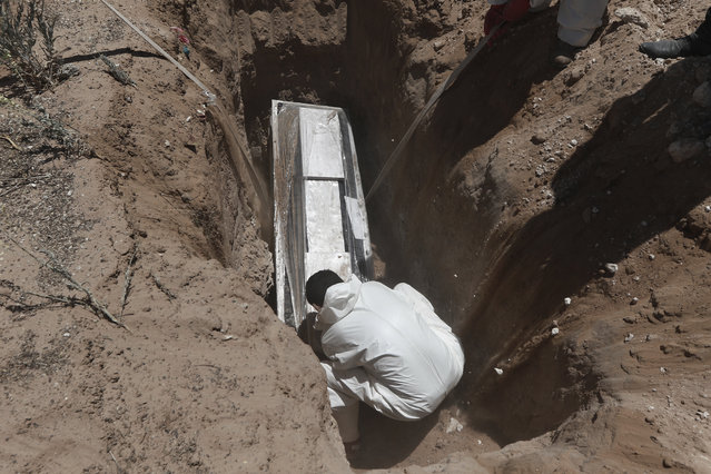 A worker wearing a protection suit against the spread of the new coronavirus buries a coffin in an area of the San Rafael municipal cemetery set apart for COVID-19 cases in Ciudad Juarez, Mexico, Tuesday, May 19, 2020. (Photo by Christian Chavez/AP Photo)