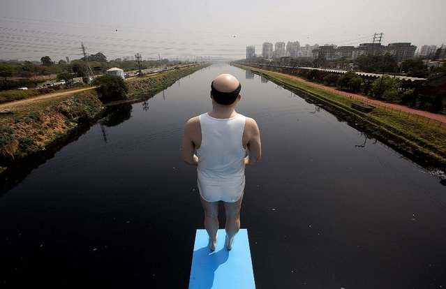 An art installation by Brazilian artist Eduardo Srur shows a life-size mannequin standing over the highly polluted Pinheiros River in Sao Paulo, Brazi, on September 18, 2014. (Photo by Andre Penner/AP Photo)