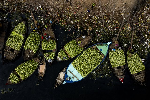 This aerial picture shows workers onloading watermelons from boats in Burigonga river during a government-imposed lockdown as a preventative measure against the spread of the COVID-19 coronavirus in Dhaka on April 17, 2020. (Photo by Munir Uz Zaman/AFP Photo)