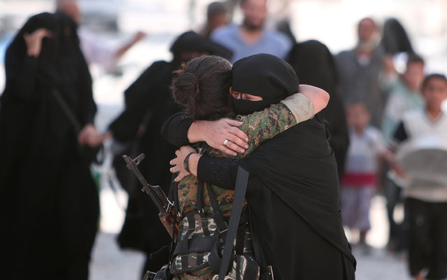 A woman embraces a Syria Democratic Forces (SDF) fighter after she was evacuated with others by the SDF from an Islamic State-controlled neighbourhood of Manbij, in Aleppo Governorate, Syria, August 12, 2016. (Photo by Rodi Said/Reuters)