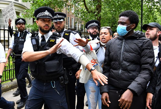 """Protesters react next to police officers in London during a """"Black Lives Matter"""" protest following the death of George Floyd who died in police custody in Minneapolis, London, Britain, June 3, 2020. (Photo by Dylan Martinez/Reuters)"""