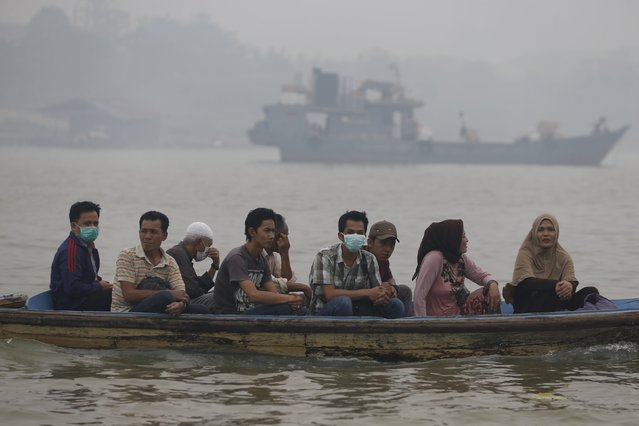 People sit on a wooden boat as they cross the haze shrouded Batanghari River in Jambi, Indonesia Sumatra island, September 14, 2015. (Photo by Reuters/Beawiharta)