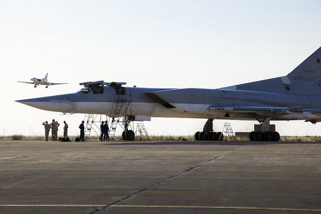 In this photo taken on Monday, Aug. 15, 2016, a Russian Tu-22M3 bomber stands on the tarmac while another plane lands at an air base near Hamedan, Iran.  Russian warplanes took off on Tuesday August 16, from Iran to target Islamic State fighters and other militants in Syria, widening Moscow's bombing campaign in Syria.(Photo by WarfareWW Photo via AP Photo)