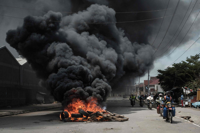 Motorcyclists pass a burning tyre barricade following a demonstration by Kenyan opposition party National Super Alliance (NASA) supporters on November 17, 2017 in Nairobi. Opposition leader Raila Odinga returned to Kenya on November 17 only to have his welcome party in Nairobi broken up by police firing tear gas at his convoy and supporters, an AFP reporter saw. (Photo by Yasuyoshi Chiba/AFP Photo)