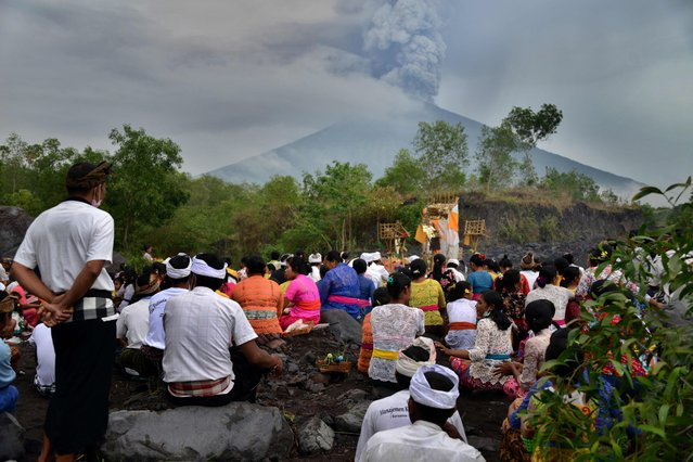 Balinese Hindus take part in a ceremony, where they pray near Mount Agung in hope of preventing a volcanic eruption, in Muntig village of the Kubu sub-district in Karangasem Regency on Indonesia's resort island of Bali on November 26, 2017. A volcano on the Indonesian tourist island of Bali sent plumes of grey smoke and steam thousands of metres into the air on November 26 for the third day  in a week, triggering flight cancellations which have left thousands of tourists stranded, officials said Sunday. (Photo by Sonny Tumbelaka/AFP Photo)