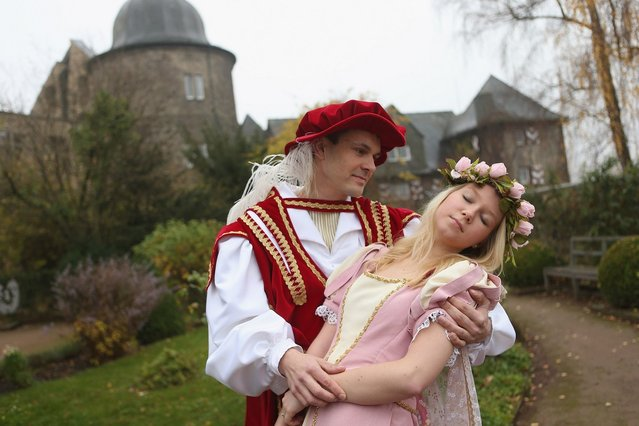 """HOFGEISMAR, GERMANY - NOVEMBER 18:  Prince Charming, actually actor Andreas Richhardt, supports Sleeping Beauty, played by actress Elisabeth Knoche, at Sababurg Palace on November 18, 2012 near Hofgeismar, Germany. Sleeping Beauty (in German: Dornroeschen) is one of the many stories featured in the collection of fairy tales collected by the Grimm brothers, and the 200th anniversary of the first publication of the stories will take place this coming December 20th. Andreas and Elisabeth perform a skit based on the Sleeping Beauty tale to visitors during the summer months at Sababurg, which is now a hotel called Dornroeschenschloss Sababurg and is located along the """"Fairy Tale Road"""" (""""Maerchenstrasse"""") from where many of the tales derive. The Grimm brothers collected their stories from oral traditions in the region between Frankfurt and Bremen in the early 19th century, and the works include such global classics as Rapunzel, Little Red Riding Hood, The Pied Piper of Hamelin, Cinderella and Hansel and Gretel.  (Photo by Sean Gallup)"""