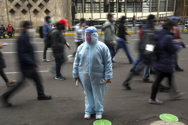 A woman waits outside a shop wearing protective gear due to the COVID-19 pandemic in downtown Lima, Peru, Monday, July 6, 2020. (Photo by Rodrigo Abd/AP Photo)