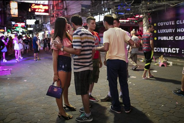 A bar girl negotiates with men for her services along the Walking Street where bars and s*x scenes are a commonplace July 31, 2016 in Pattaya, Thailand. (Photo by Tsering Topgyal/AP Photo)
