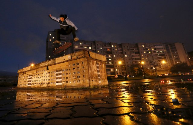 "Local skateboarder Markel Andronov jumps over an art work by a German street artist who goes by the name ""Evol"", in central Krasnoyarsk, Siberia, Russia, September 24, 2015. The artwork was created for the 11th Krasnoyarsk Museum Biennale, which will open September 30, with artists from Russia, the Unites States, Germany, Poland, Great Britain, Netherlands and other countries attending, according to organizers. (Photo by Ilya Naymushin/Reuters)"