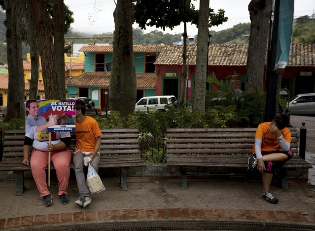 In this Thursday, December 7, 2017 photo, supporters of opposition mayoral candidate Yon Goicoechea wait for the start of a campaign rally, in Caracas, Venezuela. Still bruising from a shock defeat in recent gubernatorial races, the opposition is limping into Sunday's vote deeply divided, with three of the four biggest parties in the Democratic Unity coalition boycotting the race altogether. (Photo by Fernando Llano/AP Photo)