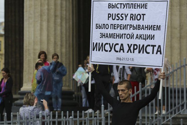 """Artist Pyotr Pavlensky holds a board in support of jailed members of female punk band """"p*ssy Riot"""" with his mouth sewn shut during a protest in St. Petersburg, July 23, 2012. (Photo by Reuters/Trend Photo Agency)"""