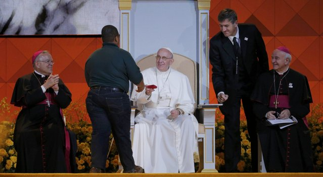 Pope Francis gives a present to a boy as he attends the Festival of Families in Philadelphia, Pennsylvania September 26, 2015. (Photo by Brian Snyder/Reuters)