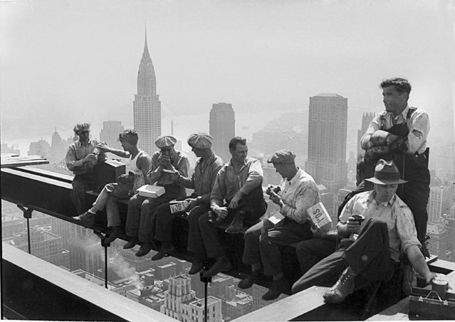 Construction workers take a lunch break on a steel beam atop the RCA Building at Rockefeller Center, New York, September 29, 1932. In the background is the Chrysler Building. (Photo by AP Photo)