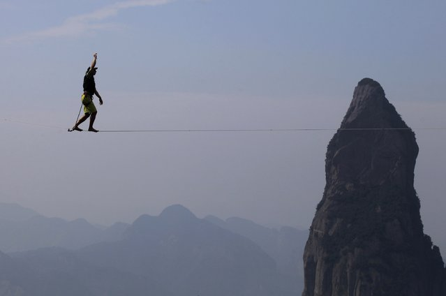 Damian Jorren of Germany walks on a slackline during a show at Shenxianju in Taizhou, October 18, 2014. (Photo by Reuters/Stringer)