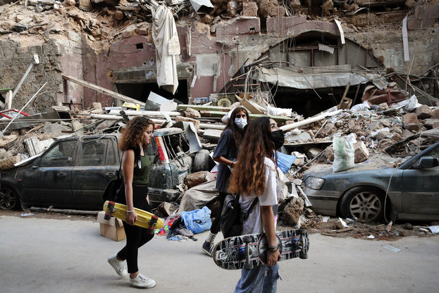 Women walk past destroyed cars at a neighborhood near the scene of Tuesday's explosion that hit the seaport of Beirut, Lebanon, Friday, August 7, 2020. Rescue teams were still searching the rubble of Beirut's port for bodies on Friday, nearly three days after a massive explosion sent a wave of destruction through Lebanon's capital. (Photo by Thibault Camus/AP Photo)