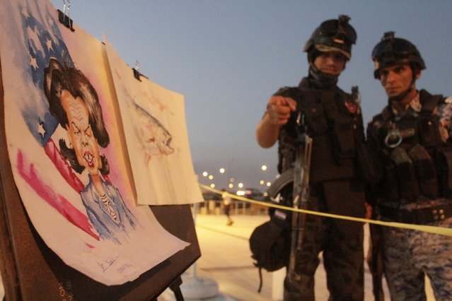 "Iraqi security forces look at a drawing in Basra, southeast of Baghdad, October 24, 2014. A group of young artists in Basra have formed a group called ""Sumerians for Art"" to give free lessons to beginner painters and drawers in Iraq's southern city. (Photo by Essam Al-Sudani/Reuters)"