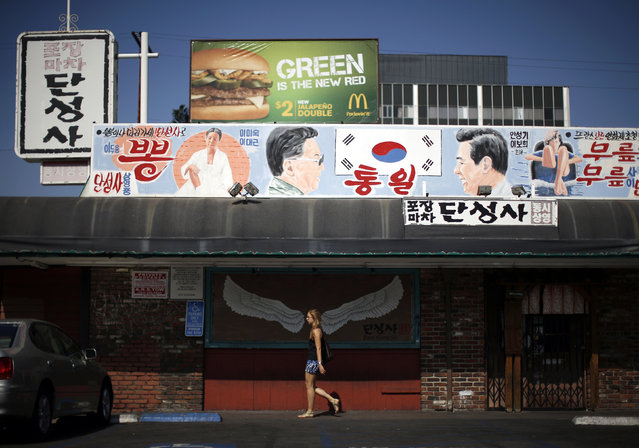 A woman walks past a mural of a pair of wings, under another mural depicting former North Korean leader Kim Jong Il (2nd L) and former South Korean president Kim Dae-jung (2nd R) on either side of a South Korean flag, hanging above Dan Sung Sa restaurant and bar in the Koreatown area of Los Angeles, California August 14, 2014. (Photo by Lucy Nicholson/Reuters)