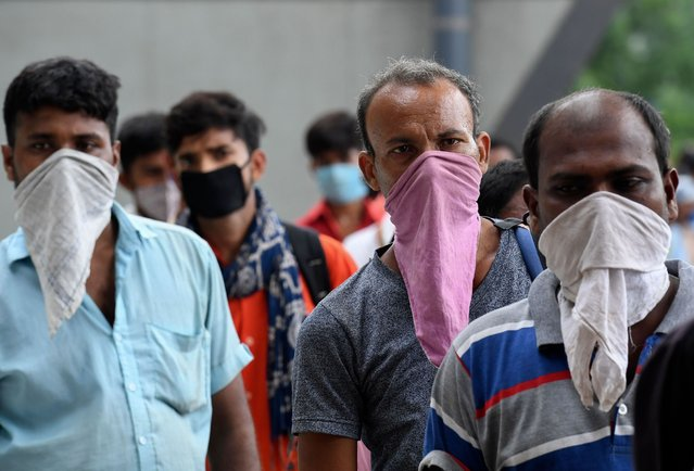 Migrant workers coming from other states, stand in queue to get a Rapid Antigen Test (RAT) for the COVID-19 coronavirus as they arrived at the Anand Vihar bus terminal to board on city buses, in New Delhi on August 18, 2020. India's official coronavirus death soared past 50,000 on August 17 as the pandemic rages through smaller cities and rural areas where health care is feeble and stigmatisation rife. (Photo by Prakash Singh/AFP Photo)