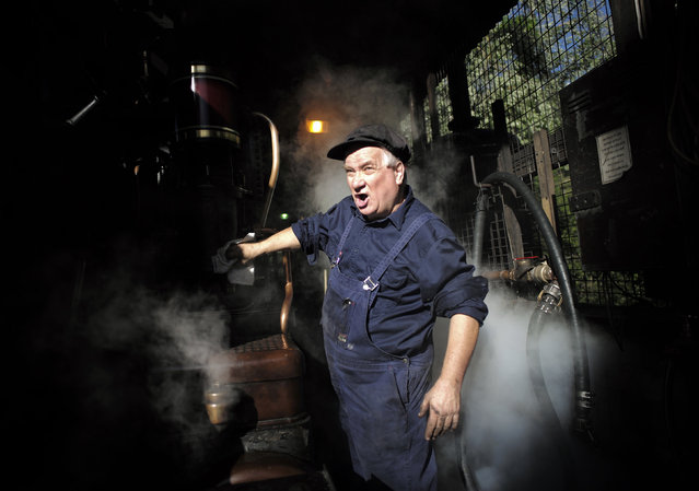 Puffing Billy steam engine driver Steve Holmes, 61, wipes down locomotive 12A as it gets up to steam before running his train from Belgrave station near Melbourne, October 20, 2014. (Photo by Jason Reed/Reuters)