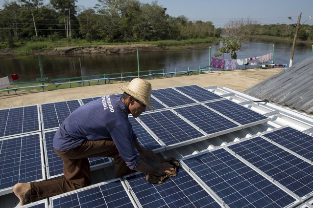 Francisco da Silva Vale, 61, cleans solar panels which power ice machines at Vila Nova do Amana community in the Sustainable Development Reserve, in Amazonas state,  Brazil, September 22, 2015. (Photo by Bruno Kelly/Reuters)