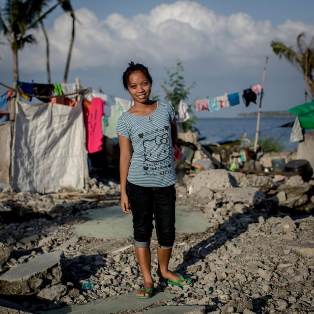 Typhoon Haiyan survivor Jessica Flores Vevera stands amongst the ruins of her family home on November 6, 2014 in San Jose, Leyte, Philippines. Jessica has lived with two families in a tent on the site for the past year and has received a permanent house from and NGO and is waiting for it to be completed before moving. (Photo by Chris McGrath/Getty Images)