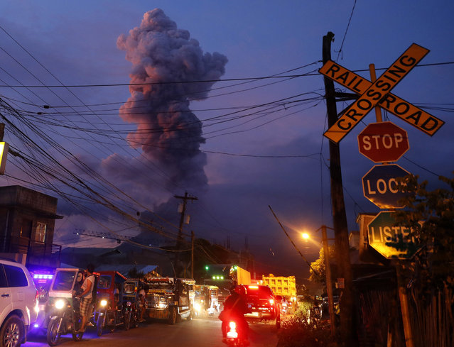 A view of Mayon Volcano erupts anew in the town of Daraga, Albay province, Philippines, 24 January 2018. Mayon volcano located in eastern Philippines and active over the last 10 days spewed fresh lava and ash in two new eruptions a day earlier. The number of evacuees exceeded 60 thousand in the face of the threat of an even more potent explosion. The Philippines, which currently has 23 active volcanoes, is situated on the so-called 'Pacific Ring of Fire', an area known for its intense seismic activity which extends from the west coast of the American continent to New Zealand, Japan, the Philippines and Indonesia. (Photo by Francis R. Malasig/EPA/EFE)