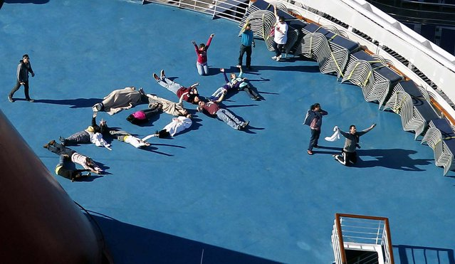 "Passengers spell out the word ""HELP"" aboard the disabled Carnival Lines cruise ship Triumph as it is towed to harbor, February 14, 2013. (Photo by Gerald Herbert/Associated Press)"