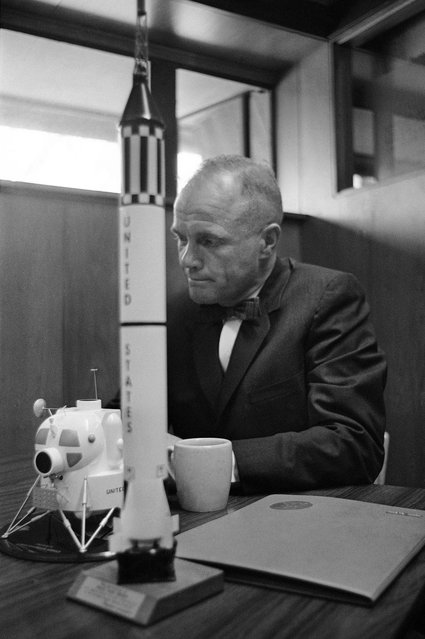 In this February 8, 1963 file photo, astronaut John Glenn sits with models of the Mercury spacecraft atop its launch rocket and a lunar module, representing the past and the future of space exploration as he talks about the first anniversary of his historic flight. (Photo by AFP Photo)