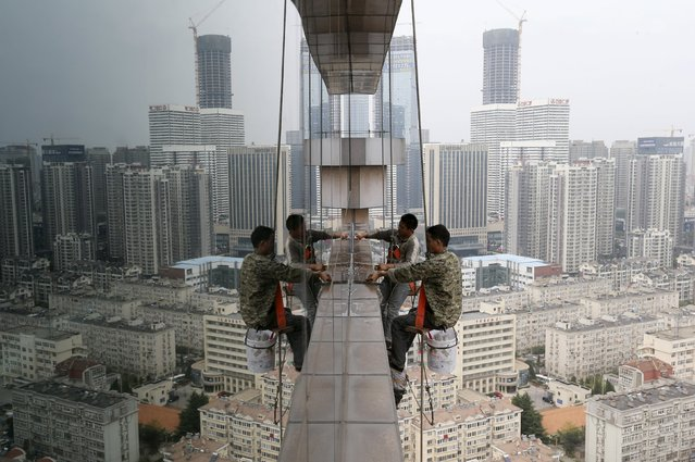 Labourers clean the glass windows outside a 30-floor business building in Qingdao, Shandong province, China, October 4, 2015. A deluge of data from China in coming weeks is likely to point to further weakness in the world's second-largest economy, reinforcing expectations that Beijing will roll out more stimulus measures to ward off a sharper slowdown. (Photo by Reuters/Stringer)