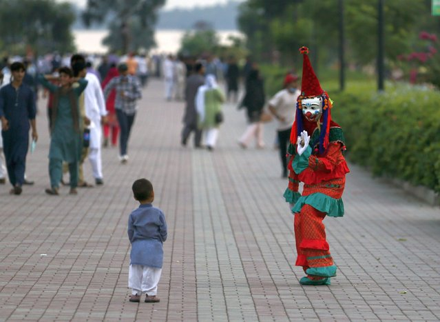 A clown interacts with a child visiting Lake View park with his family on the outskirts of Islamabad, Pakistan on Wednesday, September 9, 2020. Lake View Park, alongside the Rawal Lake, has become a favorite picnic spot for Pakistani and foreign tourists. (Photo by Anjum Naveed/AP Photo)