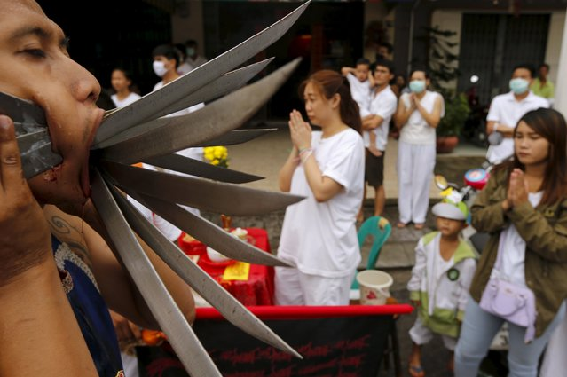 A devotee of the Chinese Bang Neow shrine with knives pierced through his cheeks walks during a procession celebrating the annual vegetarian festival in Phuket, Thailand October 18, 2015. (Photo by Jorge Silva/Reuters)