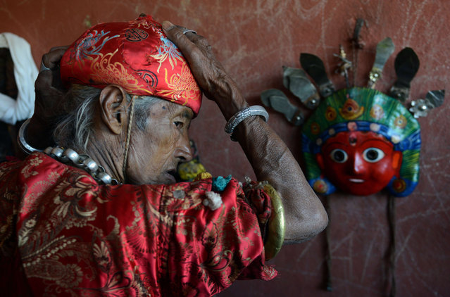 A Nepalese Hindu devotee dresses as a deity as he prepares to participate in festivities at the Shikali Temple during celebrations for the Shikali Jatra festival in the village of Khokana, on the outskirts of Kathmandu, on October 19, 2015. Local villagers, who normally do not celebrate the country's most famous festival of Dashain, celebrate the Shikali Jatra each year. (Photo by Prakash Mathema/AFP Photo)