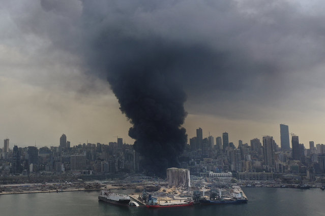 Black smoke rises from a fire at warehouses at the seaport of Beirut, Lebanon, Thursday, September 10. 2020. A huge fire broke out Thursday at the Port of Beirut, triggering panic among residents traumatized by last month's massive explosion that killed and injured thousands of people. (Photo by Hussein Malla/AP Photo)