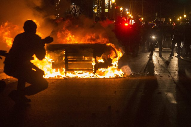 Police are seen near a burning police vehicle after a grand jury returned no indictment in the shooting of Michael Brown in Ferguson, Missouri, November 24, 2014. (Photo by Adrees Latif/Reuters)