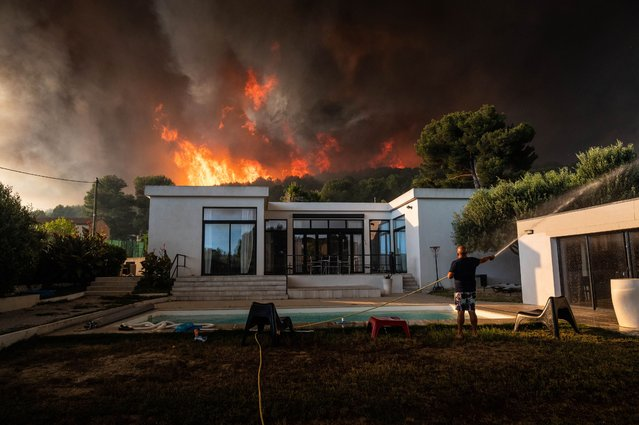 A man uses a garden hose to drench his house before being evacuated as a wild fire burns in the background, in La Couronne, near Marseille, on August 4, 2020. Several fires were raging on August 4 evening near Marseille, with one particularly fuelled by strong winds, ravaging nearly 300 hectares of vegetation in a coastal area of Martigues, according to the authorities. (Photo by Xavier Leoty/AFP Photo)