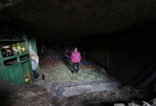 A displaced girl poses inside an underground cave in Jabal al-Zawiya in the southern countryside of Idlib November 26, 2014. (Photo by Khalil Ashawi/Reuters)