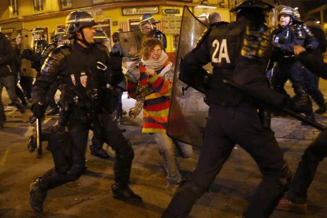 A protester clashes with French riot police during a demonstration against police brutality in Nantes, western France, November 22, 2014. People protest against the use of force by police and in memory of 21-year-old environmentalist Remi Fraisse who died during a violent stand-off over the weekend October 25-26 between police and ecology protesters seeking to prevent construction of a dam in Sivens. (Photo by Stephane Mahe/Reuters)