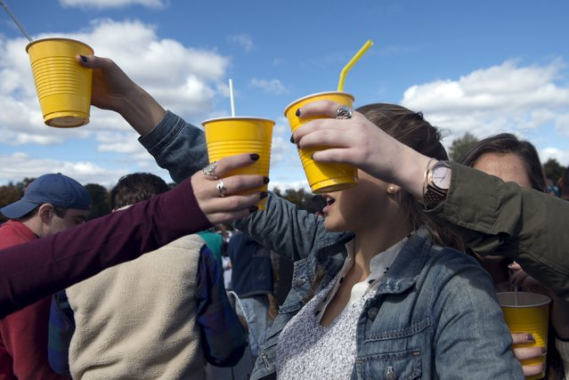 Revellers hold up yellow plastic cups at the Far Hills Race Day at Moorland Farms in Far Hills, New Jersey, October 17, 2015. (Photo by Stephanie Keith/Reuters)